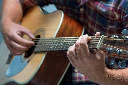 pria sedang bermain gitar