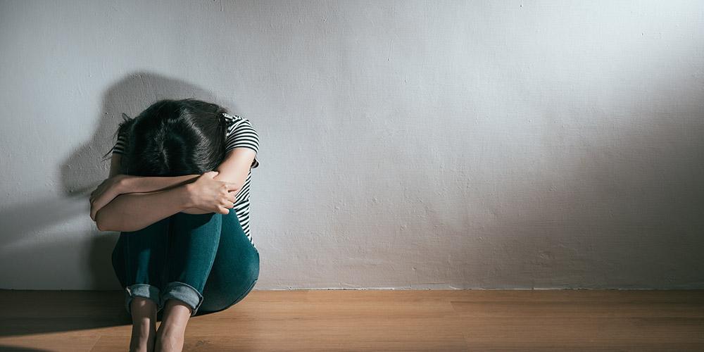 seorang wanita sedang tertunduk sedih