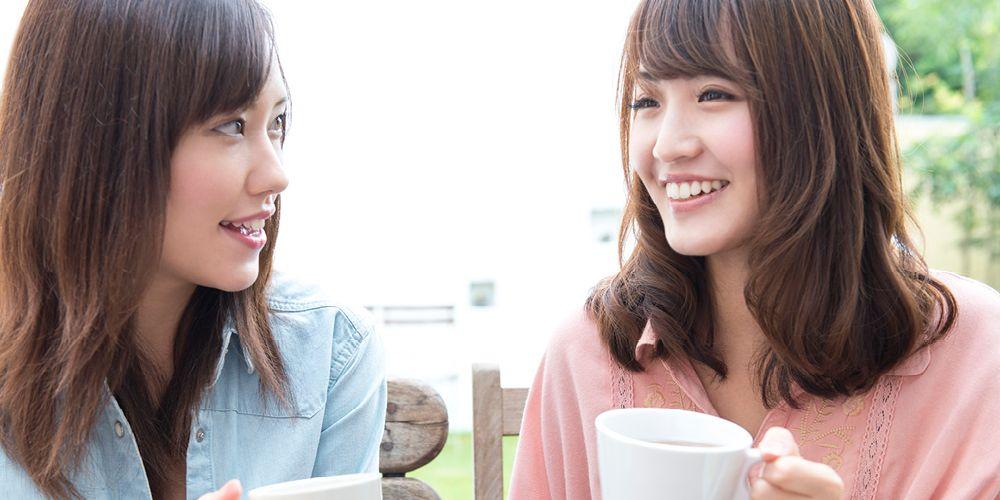 Dua perempuan sedang berbicara sambil memegang kopi