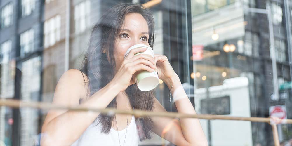 Seorang perempuan meminum kopi