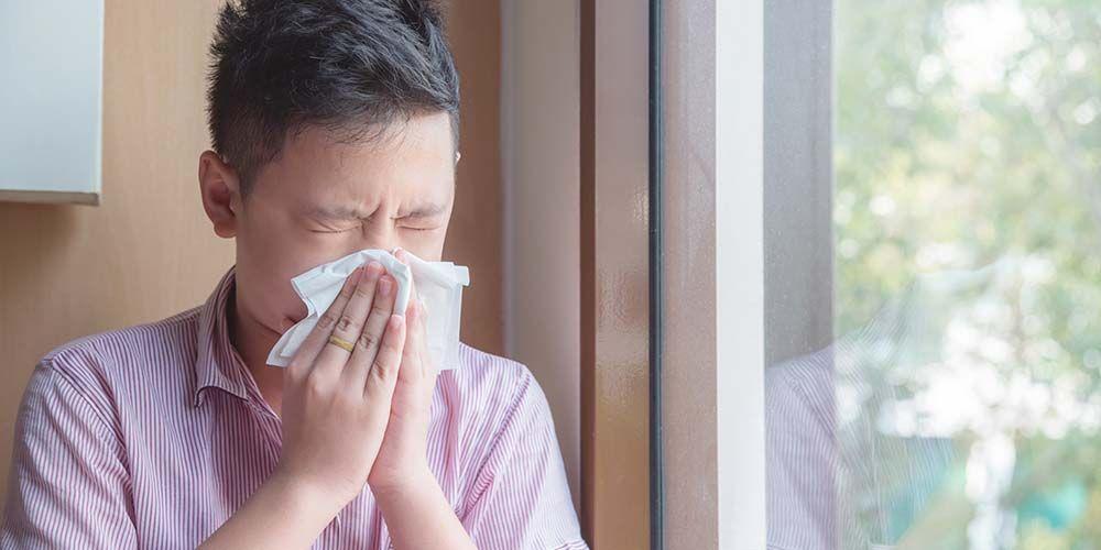 seorang pria sedang  bersin karena alergi