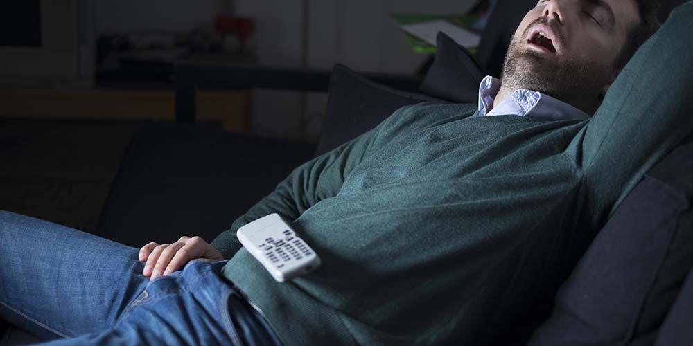 seorang pria tidur di sofa