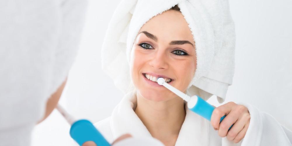 Seorang wanita sedang menggunakan sikat gigi elektrik