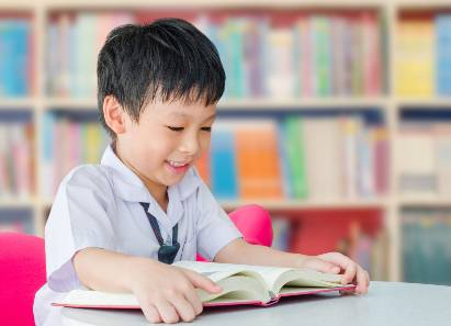 Seorang anak sedang membaca buku di sekolah