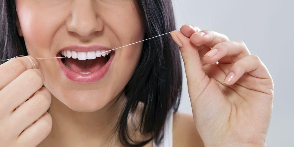 Cara mengatasi bau mulut saat puasa dengan membersihkan gigi menggunakan benang gigi