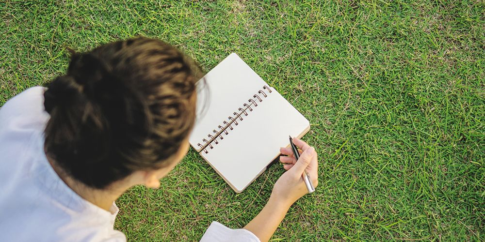 seorang perempuan sedang menulis diari