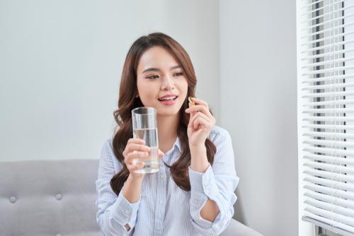 wanita minum suplemen daya tahan tubuh