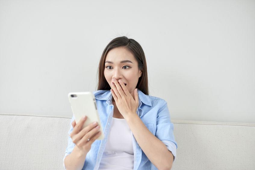 wanita terkejut membaca pesan di hp