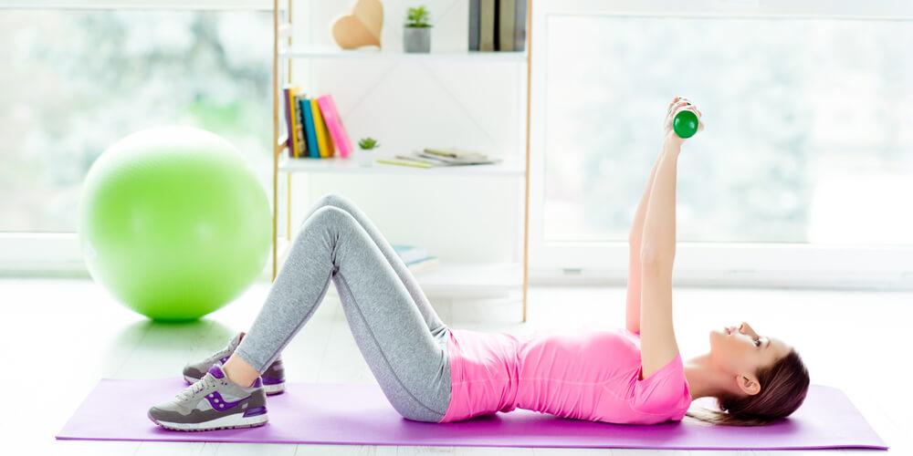 Cara membesarkan payudara dengan mengangkat dumbbell